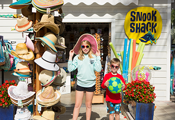 Two kids standing outside of the Snook Shack beside a hat rack.