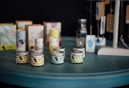 Products lined up on a turquoise table in Ambu Boutique.