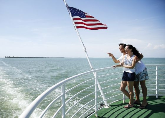 A couple pointing to something in the distance while leaning against a boat railing.