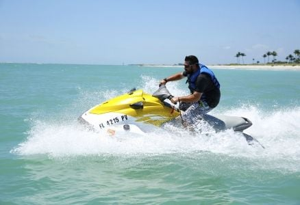 A man wearing a blue life jacket on a jet ski.