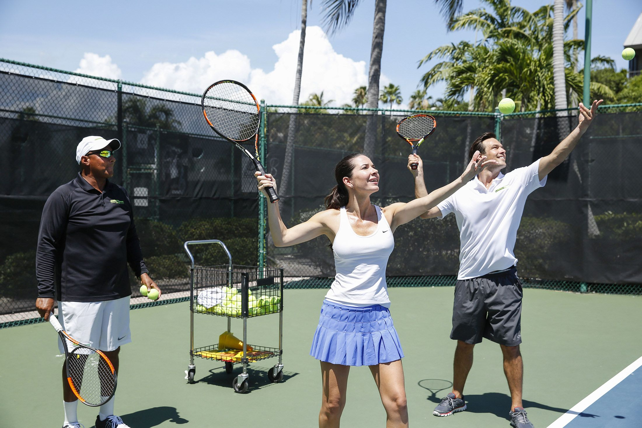 A couple learning to serve on a Sanibel tennis court