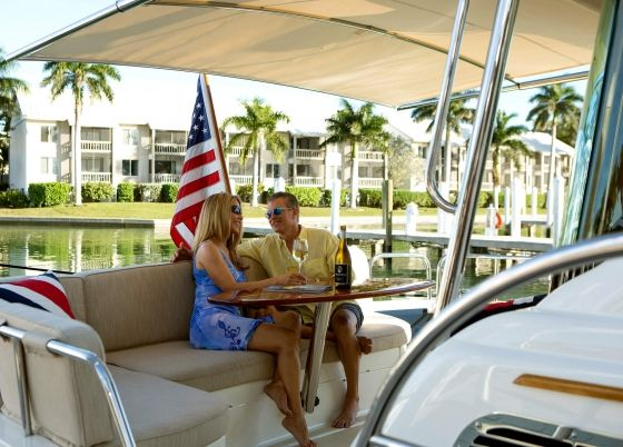 A couple sits together drinking wine on a boat.