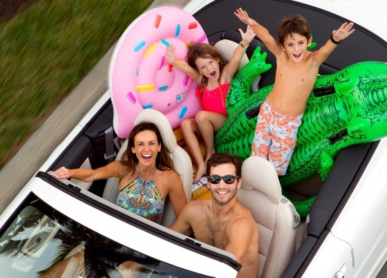 A family in a white convertible posing for the camera.