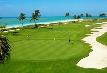 A lush golf course along a white-sand beach.