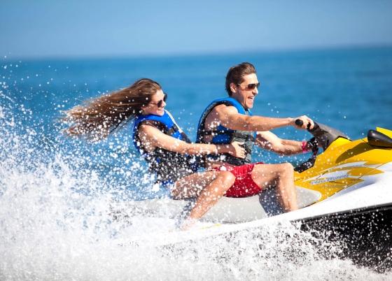A woman and man riding a jet ski.