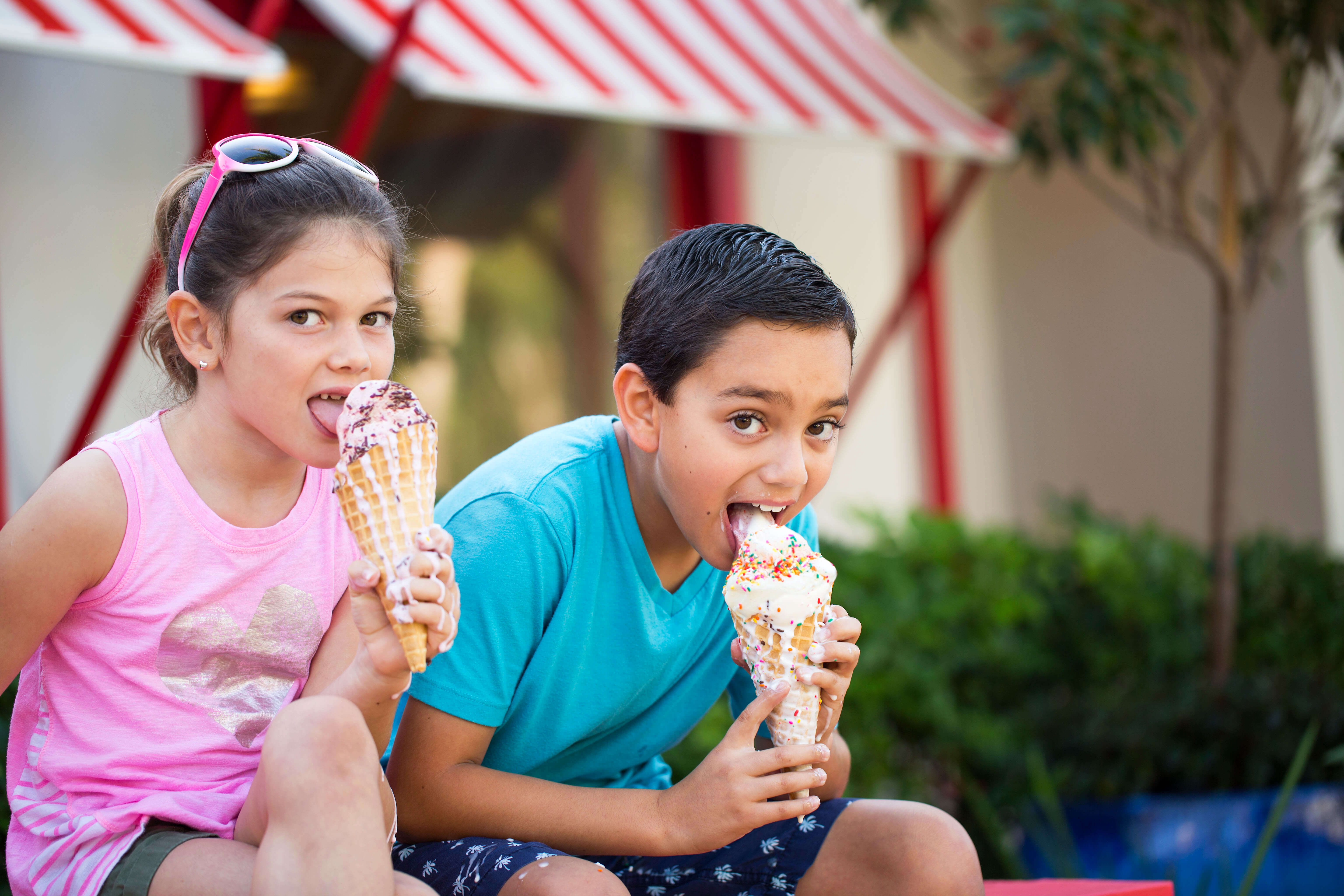 Two kids outside eating ice cream.