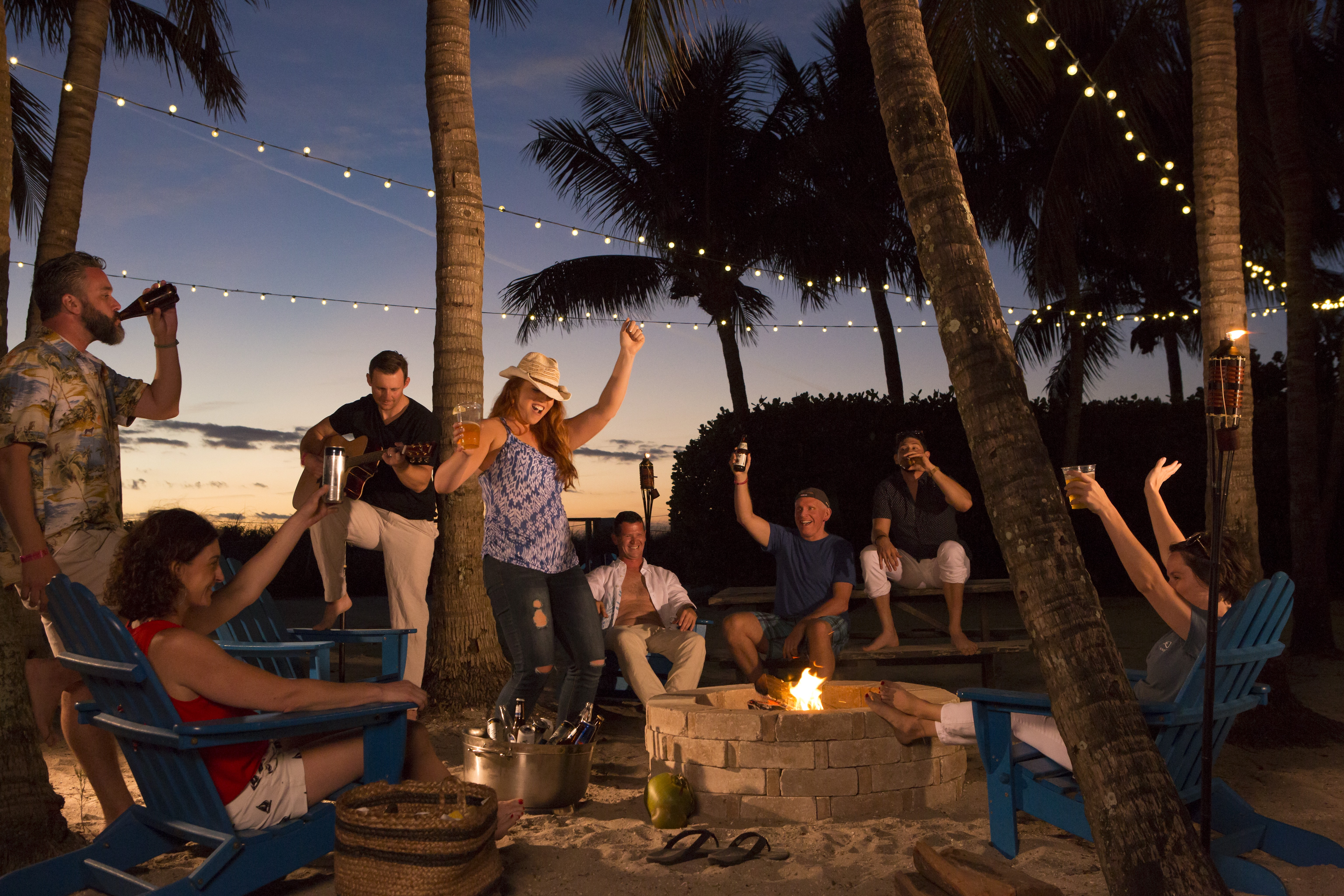 Guests dancing around the firepit at sunset.