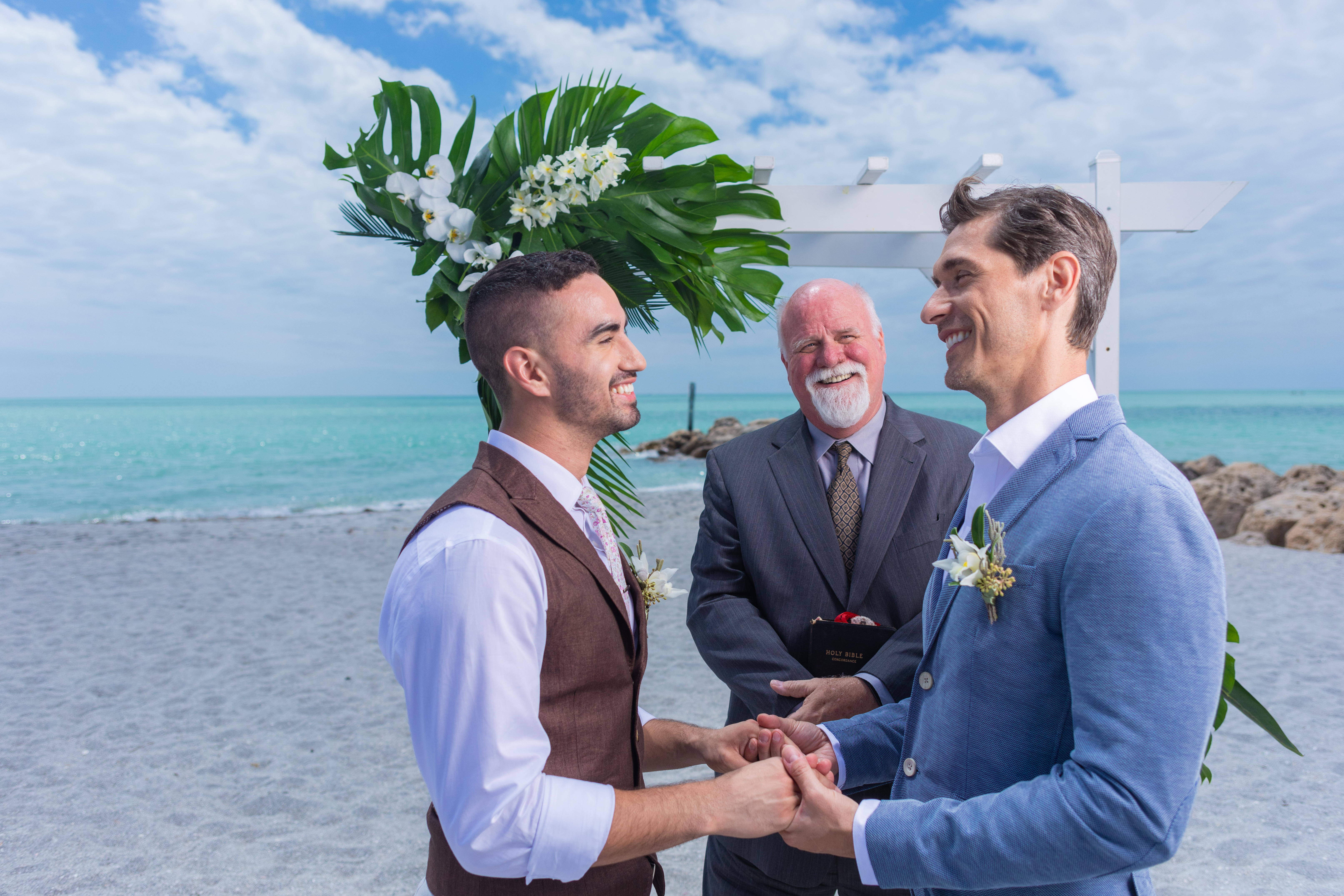 Gay Couple with Officiant at Wedding on the Beach