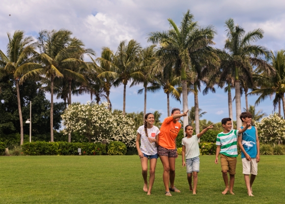A family walks across the grounds of South Seas Resort as palm trees sway in the background