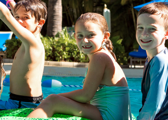 Kids smile while playing in a pool.